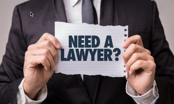 Man holding sign says Need A Lawyer?